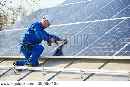 Male Worker In Blue Suit And Protective Helmet Installing Solar Photovoltaic Panel System Using Scre