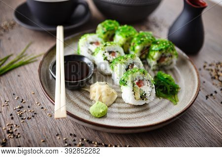 Sushi maki rolls with cucumber, avocado, tomato, creamy cheese, chuka wakame on a plate with chopsticks, soy sauce, wasabi and ginger. Japanese traditional seafood served for lunch in restaurant.
