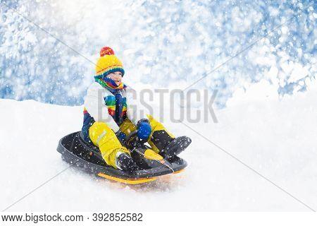 Little Boy Enjoying A Sleigh Ride. Child Sledding. Toddler Kid Riding A Sledge. Children Play Outdoo