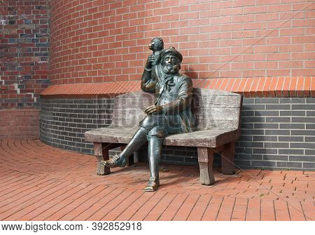 Bronze Sculpture Of A Sailor With A Monkey Installed In A Fish Village In The City Of Kaliningrad, R