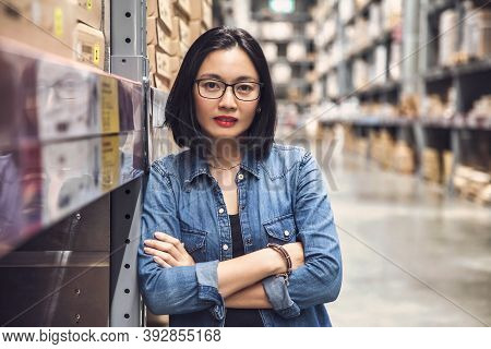 Asian Beautiful Young Woman Worker Of Furniture Store With Arms Crossed In A Large Warehouse.