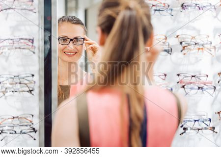 Young woman trying fashionable glasses in optometrist store looking at herself in the mirror