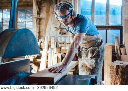 Diligent carpenter working on wood with the circular saw