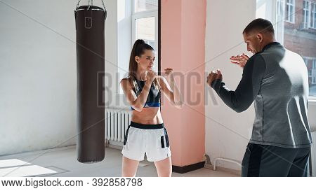 Cute Girl Learns Kickboxing Techniques In The Gym With An Experienced Trainer