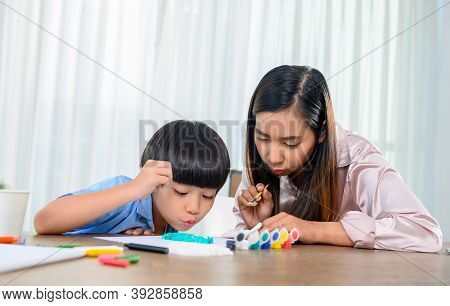 Asian Mother Work Home Together With Son. Mom And Kid Drawing Picture And Color Painting Art. Woman