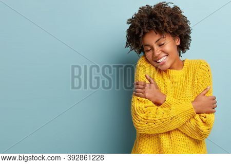 Happy Young Dark Skinned Woman Hugs Herself, Feels Warmth Cozy, Wears Yellow Knitted Sweater, Enjoys