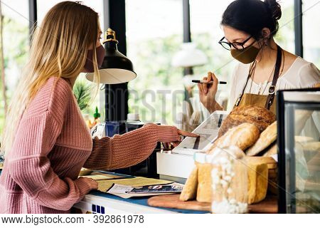 Woman wearing mask ordering food in a cafe restaurant covid 19