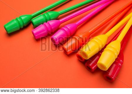 Many Colored Gymnastic Clubs Lie On An Orange Background, Concept, Close Up