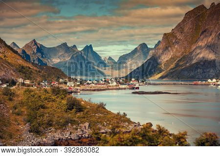 Panoramic View Of The Fishing Village Of Reine With Dramatic Sky.  Rocky Beach, Lofoten Islands, Nor