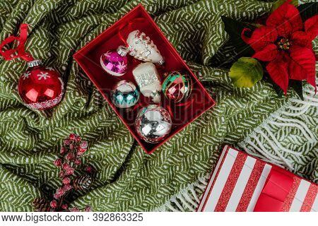 A box of Christmas ornaments on a green cloth