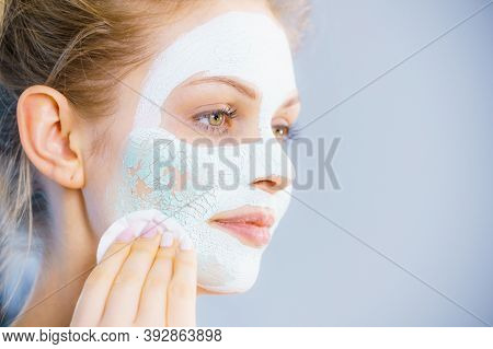 Young Woman With White Dried Mud Mask On Face Being Removing Cosmetic With Cotton Swab. Teen Girl Ta