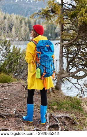 Full Length Shot Of Active Female Hiker Stands On Hill Near Mountain Lake, Wears Red Hat, Yellow Rai