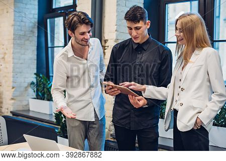 Businessmen And Businesswoman Looking On Tablet At Table In Office