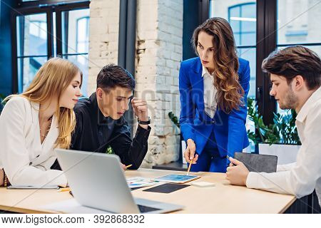 Businesswoman Showing Graph On Tablet To Colleagues At Table In Office
