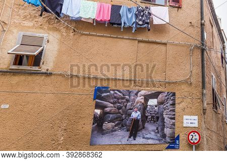 Alghero, Sardinia Island, Italy - December 28, 2019: Pictures Of 100 Year Old Residents In The Stree
