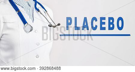 Word Placebo On A White Background. Nearby Is A Doctor In White Coat And Stethoscope. Medical Concep
