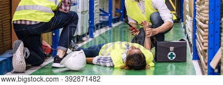 Panoramic Warehouse worker do first aid to his colleague lying down on warehouse floor after accident while working. Using for industrial safety first and business insurance concept.
