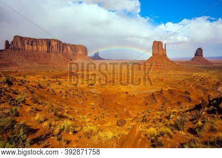The USA. Monument Valley is unique geological formation. Huge masses of red sandstone - outliers on the Navajo Indian Reservation. Magnificent rainbow across the sky. Concept of photo tourism