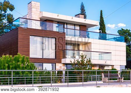 Sochi, Russia - November, 24, 2019: Facade Of A Modern Style House With Patio Glass Railing. Wooden