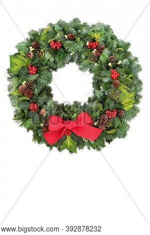Christmas spruce fir wreath with winter berry holly, mistletoe, acorns, pine cones & greenery on white background. Traditional composition for the festive season. Copy space.