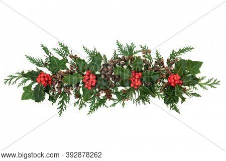 Christmas decorative display with winter berry holly, cedar cypress, ivy & pine cones forming a natural element for the festive season & New Year on white background. Flat lay, top view, copy space.