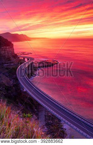 Beautiful Vivid Color Rich Red And Orange Sunrise Over Illawrra Coast With Sea Cliff Bridge Snaking