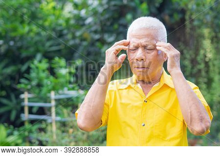Senior Man With A Headache, Feeling Pain, And With An Expression Of Being Unwell While Standing In T