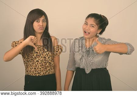 Studio Shot Of Young Happy Fat Persian Teenage Girl Smiling While Giving Thumb Up With Young Persian