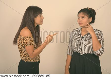 Studio Shot Of Young Angry Persian Woman Pointing At Young Fat Persian Teenage Girl Crying Against G