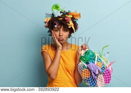 Unhappy Dark Skinned Woman Purses Lips, Has Dissatisfied Expression, Touches Cheek, Has Things Made