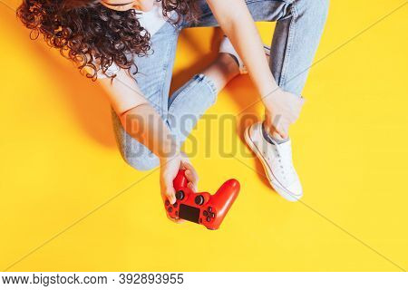 Woman Holding Gamepad In Her Hands In Against Of A Yellow Background. Promotion Of Womens Esports. A