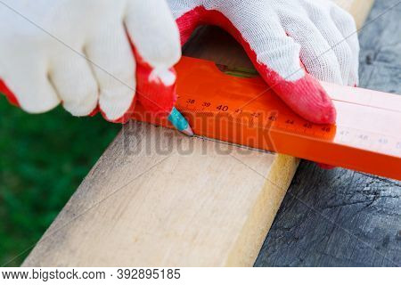 The Carpenters Hands In Work Gloves Draw A Line With A Pencil Across The Board Along A Ruler.