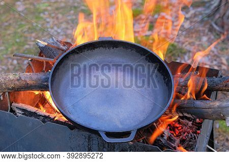 Сast Iron Skillet Over An Red Fire Heats Up For Further Cooking. Firing A Cast Iron Skillet Over An