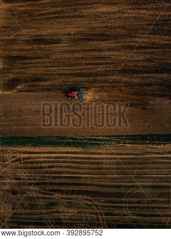 Aerial View Of Field In Which Tractor Plows.blue Tillage Equipment And Red Tractor Are Clearly Visib