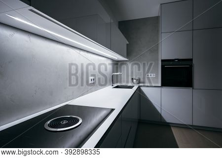 Modern Minimal Kitchen With White Worktop,bright Light Strip Turned On And Modern Appliances.focused