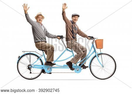 Elderly men riding a blue tandem bicycle and waving at camera isolated on white background