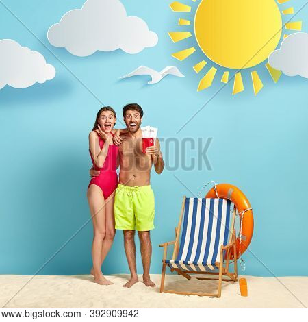Pleased Woman And Man Rejoice Having Summer Trip, Pose In Beachwear With Flying Tickets And Passport