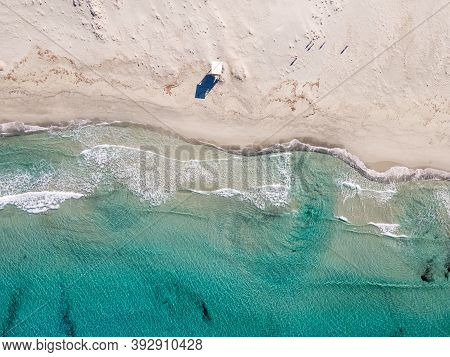 Birds-eye View Of The Waves Of The Turquoise Mediterranean Washing Onto The White Sandy Beach Of Ost