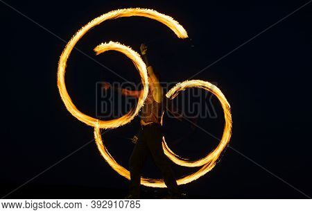 Fire Poi Artist Perform Burning Reels With Glowing, Tails In Motion On Dark Sky Outdoors, Stunt