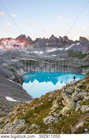 Adventurous Man Standing On Cliff Overlooking Beautiful Swiss Rockies And Wildsee Lake During A Vibr