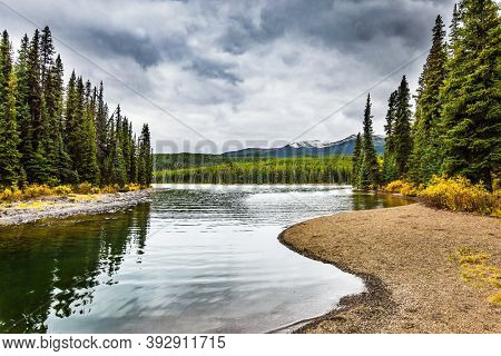 Cold cloudy fall day in the Canadian Rockies. Lake Maligne in the snow-capped mountains is surrounded by coniferous evergreen forests