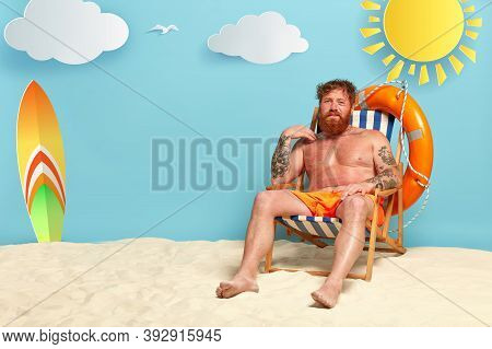 Foxy Dissatisfied Man Gets Sunburned At Beach, Has Red Skin, Sits At Sun Chair Half Naked, Has Tatto