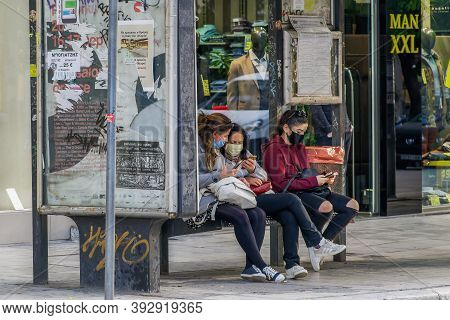 Thessaloniki, Greece - November 02 2020: People With Covid-19 Masks At A Bus Stop. Unidentified Crow