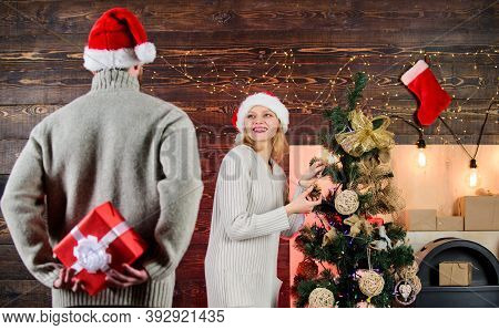 Winter Surprise. Man Carry Gift Box Behind Back. Woman Smiling Face Santa. Christmas Surprise Concep