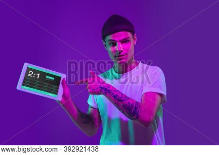 Man Holding Tablet Its Screen With Mobile App For Betting And Score, Neon Light. Male Hands Holding