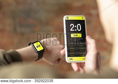 Close Up Watch And Smartphone Screen With Mobile App For Betting And Score. Male Hands Holding Devic