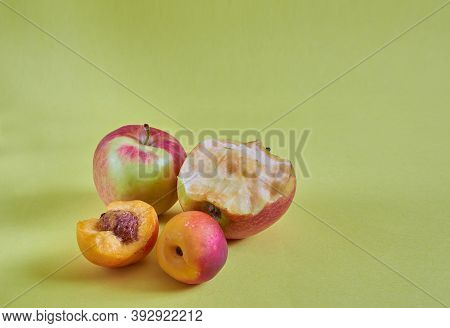 Whole And Nibbled Apples And Nectarines Lie On A Colored Background. Close Up