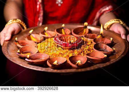 Happy Diwali Background. Indian Woman Or Bride Wearing Traditional Red Cloth And Jewelry, Holding Pu