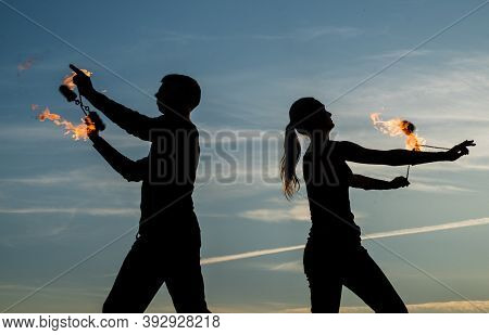 Dance All Night. Fire Dancers On Evening Sky. Couple Of Dancers Spin Flaming Poi. Fire Performance.