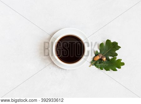 Black Coffee With Oak Leaves And Acorns On A White Background. A Cup Of Acorn Coffee. Caffeine Subst